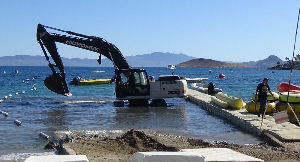 Kullandığı iş makinesiyle mavi bayraklı plaja girip, deniz dibini kazdı