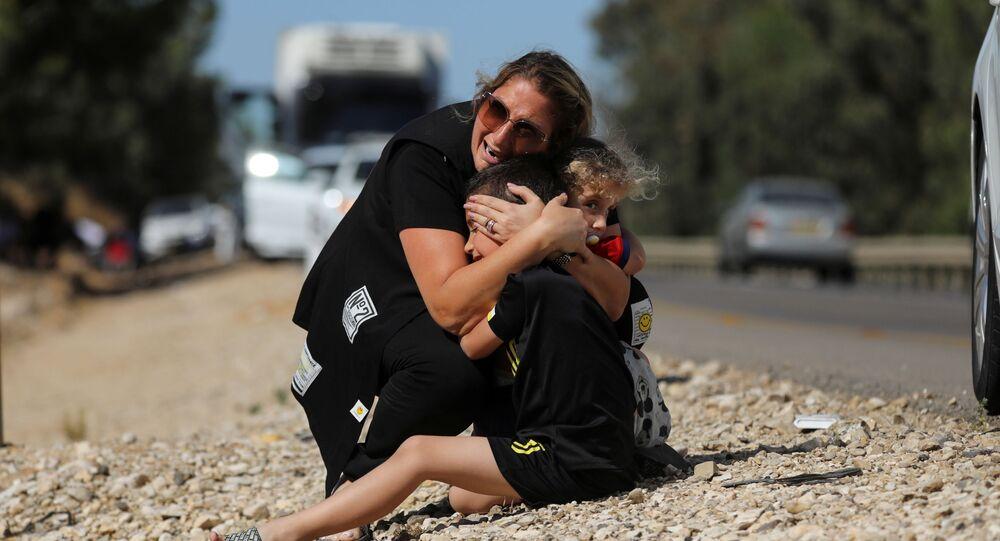 Gazze'den atılan roketler nedeniyle sirenlerin çaldığı İsrail'in Siderot kentinde çocuklarını korumaya çalışan kadın