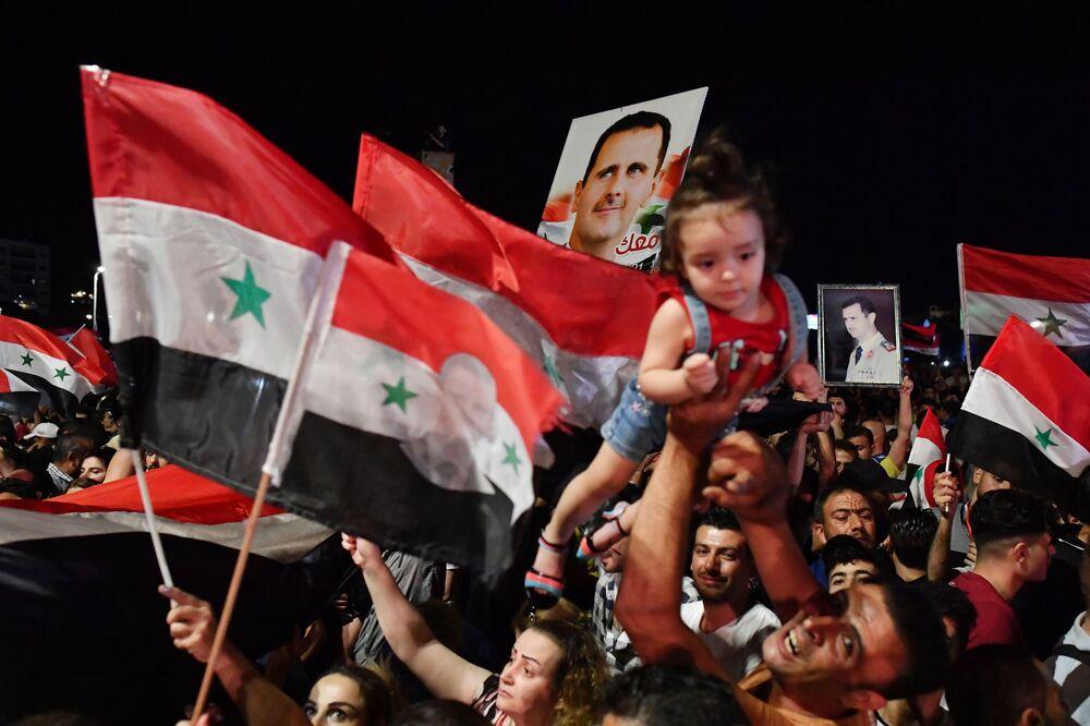 Beşar Esad'ın seçimleri kazanmasını Şam'da kutlayan Suriyeliler.