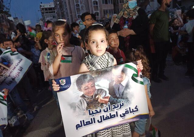 Gazze'de yaşayan Filistinli çocuklar, İsrail saldırılarında hayatını kaybeden 66 çocuğu anmak için 66 mum yaktı.