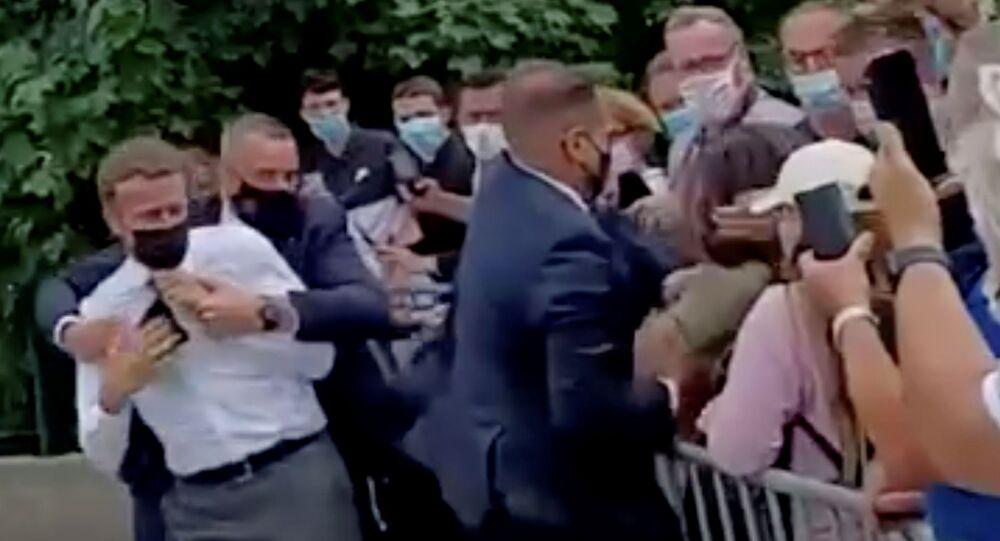 CumhurbaşkanıEmmanuel Macron, Fransa'nın  Drome bölgesinde yurttaşlarla el sıkışırken tokatlanmasının ardından korumaları tarafından uzaklaştırılırken