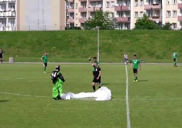 Maç ortasında sahaya inen paraşütçüye hakemden sarı kart