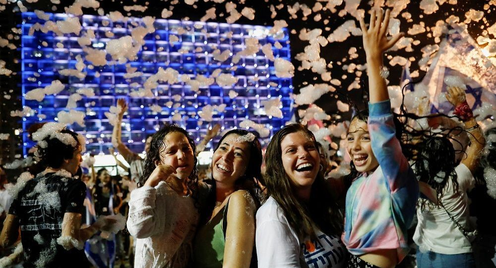 People celebrate after Israel's parliament voted in a new coalition government, ending Benjamin Netanyahu's