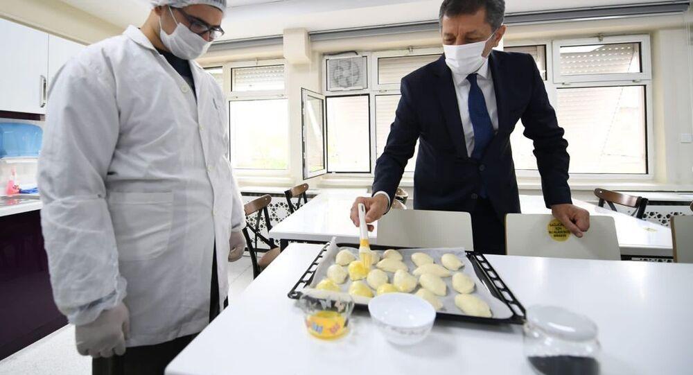 Milli Eğitim Bakanı Ziya Selçuk, Karabük'te öğrencilerle poğaça yaptı, seyyar satıcının tezgahından simit aldı.