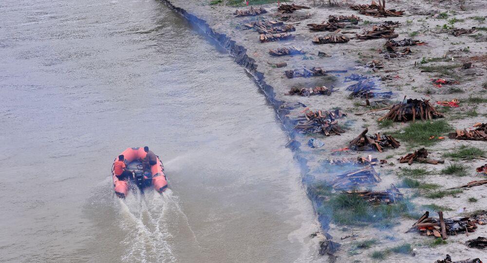 Hindistan'da şiddetli yağışın ardından Ganj Nehri yükseldi. Nehrin geri çekilmesinin ardından sahile gömülen koronavirüs kurbanlarının cesetleri yüzeye çıktı.