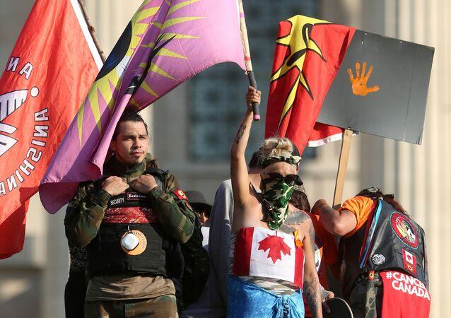 1 Temmuz Kanada Günü'nün yerli çocuk mezarlarının gölgesindekutlanmasında ısrar edilince, Winnipeg kentindeki Manitoba eyaleti parlamento binası önünde Kraliçe Victoria heykelini yıkıp kaidesine çıkan protestocular