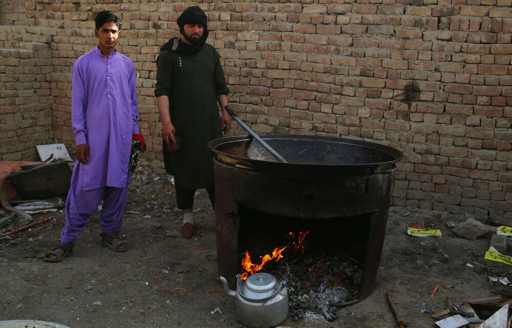 Taliban'dan kaçan  ve Kabil'deki mülteci kampına sığınan Afganlılar, yemek pişirirken