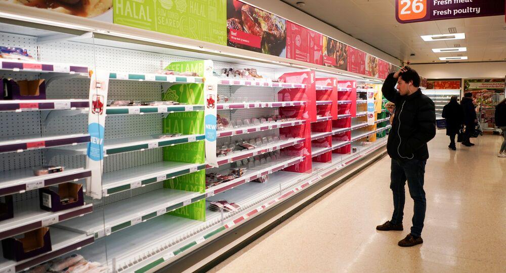 Londra'da pandeminin zirve yaptığı dönemde boş kalan süpermarket raflarına bakan bir tüketici