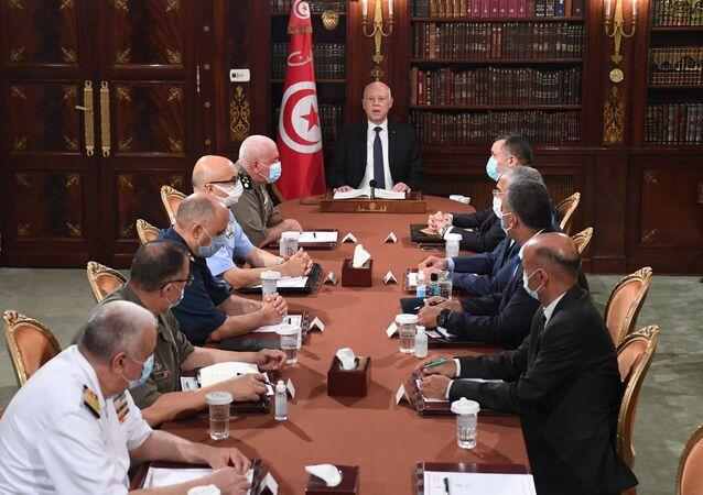Tunus'un başkenti Tunus'ta askeri komuta kademesi ve güvenlik yetkilileriyle bir araya gelen Tunus Cumhurbaşkanı Kays Said (ortada), burada yaptığı konuşmada ülkenin içinde bulunduğu olağanüstü koşullar nedeniyle meclisin tüm yetkilerini dondurduğunu, milletvekillerinin dokunulmazlığını askıya aldığını belirterek, mevcut Başbakan Hişam el-Meşişi'yi görevden aldığını ve kendi atayacağı bir başbakanla yürütmeyi devralacağını bildirdi.