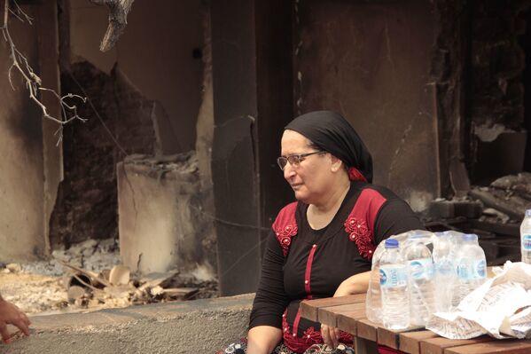 Kalemler Mahallesi'nde vatandaşlar yanan evlerin önünde oturarak yardımları bekledi. - Sputnik Türkiye