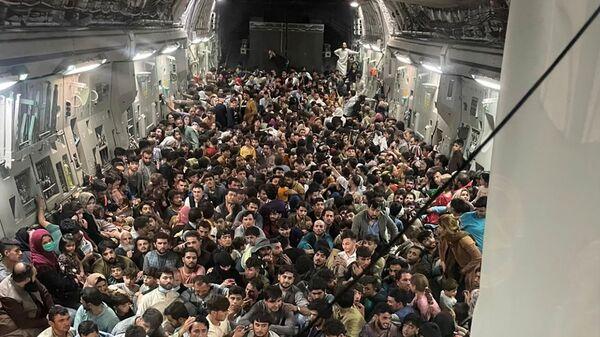 Эвакуированные в самолете ВВС США C-17 Globemaster III во время рейса Афганистан-Катар  - Sputnik Türkiye