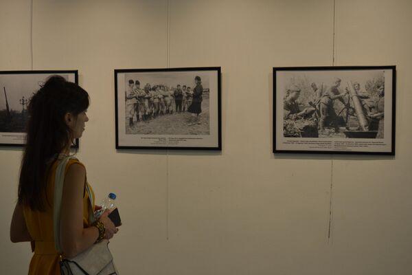 İkinci Dünya Savaşı'nın başlamasının 80. yıldönümü nedeniyle düzenlenen sinema haftası kapsamındaki fotoğraf sergisinin ziyaretçi. - Sputnik Türkiye