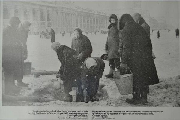 'Kuşatılmış Leninrada sakinleri, bombardıman neticesinde Nevskiy Caddesinin asfaltında oluşan deliklerde suyu topluyor' adlı bir fotoğraf.  - Sputnik Türkiye