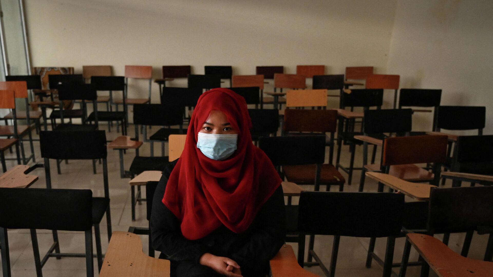 Taliban'ın kontrolündeki Afganistan'da yeniden açılan özel üniversitelerde çarşaf-peçe zorunluluğuna uymaya çalışan bir kadın öğrenci - Sputnik Türkiye, 1920, 13.09.2021