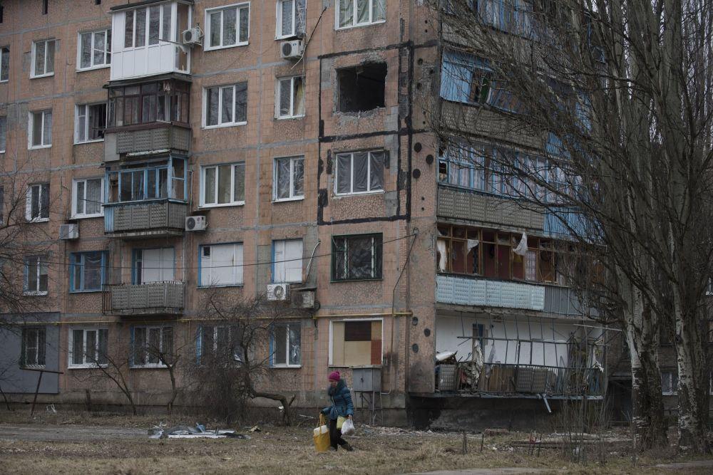 Bir kadın, Avdeyevka kentinde çatışmalar nedeniyle yıkılan çok katlı apartman binasının önünden geçiyor