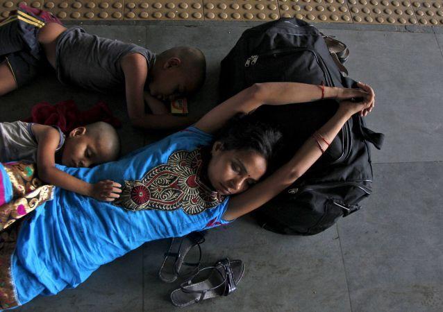 Hindistan'da tren istasyonunda uyuyan yolcular