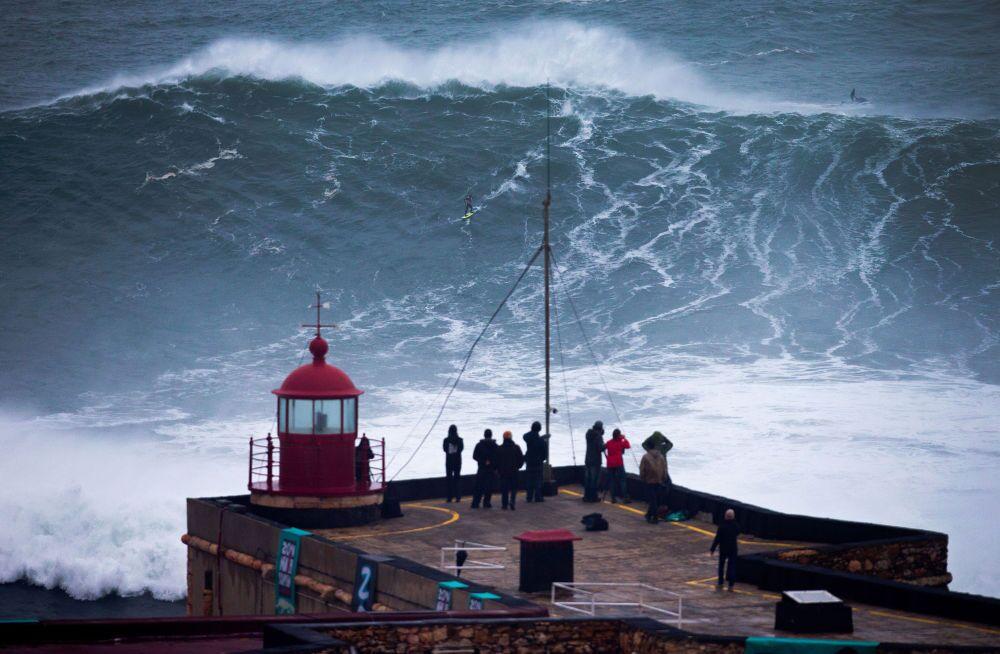 Portekiz'de insanlar, Atlas Okyanusu'nun büyük dalgalarında kayan sörfçüyü izliyor