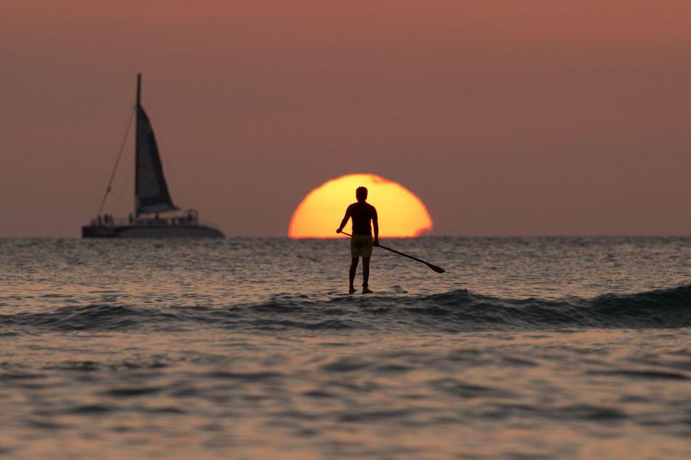 Bir sörfçü, günbatımı sırasında Pasifik Okyanusu'nda