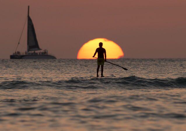 Bir sörfçu günbatımı sırasında Pasifik Okyanusu'nda