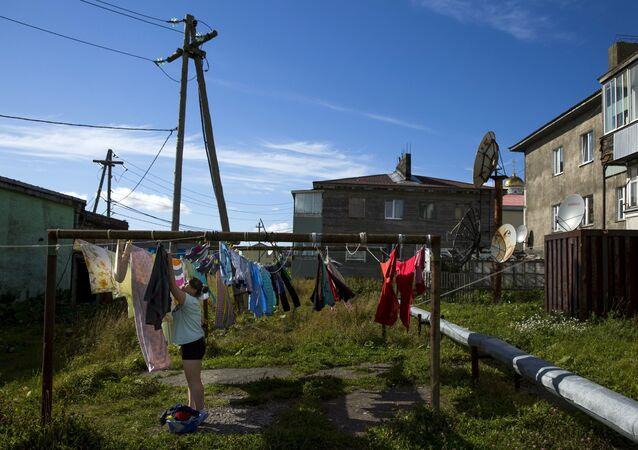 Yujno-Kurilsk'in merkezinde bir kadın çamaşır asarken.