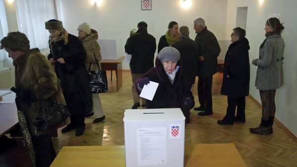 A woman casts her ballot at a polling station during the presidential election in Zagreb - Sputnik Türkiye