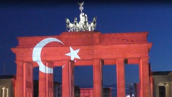 Almanya'daki Brandenburg Kapısı, Atatürk Havalimanı'ndaki saldırının ardından kırmızı-beyaz renklerle aydınlatıldı. - Sputnik Türkiye