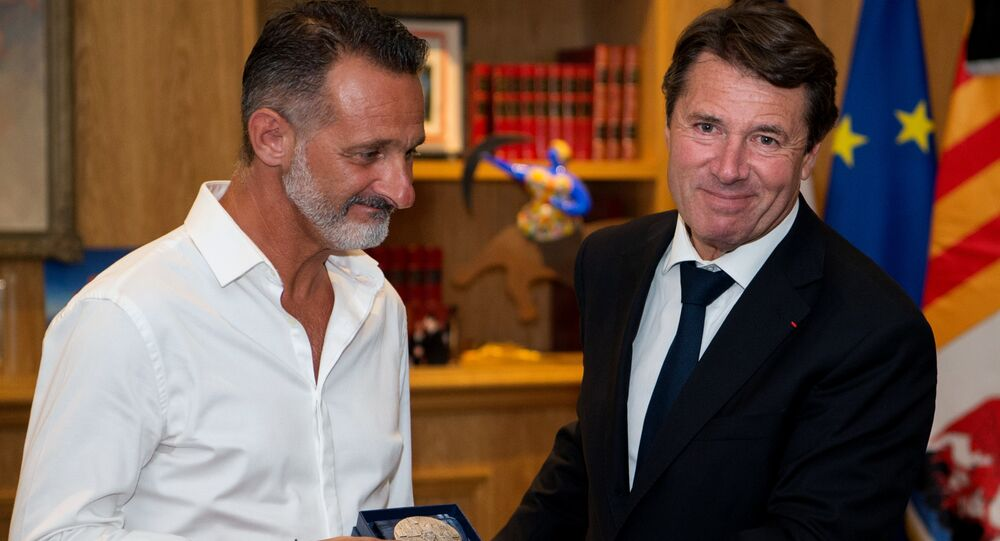 President of the Provence Alpes Cote d'Azur region and former Nice mayor Christian Estrosi (R) gives to Franck, one of the three 'heroes' of the July 14 attack in Nice, the city's medal at the City hall in Nice, southeastern France
