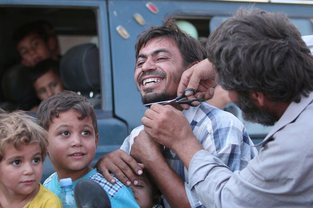 Kentin IŞİD'in elinden kurtarılmasının ardından sakallarını kesen bir Menbiçli.