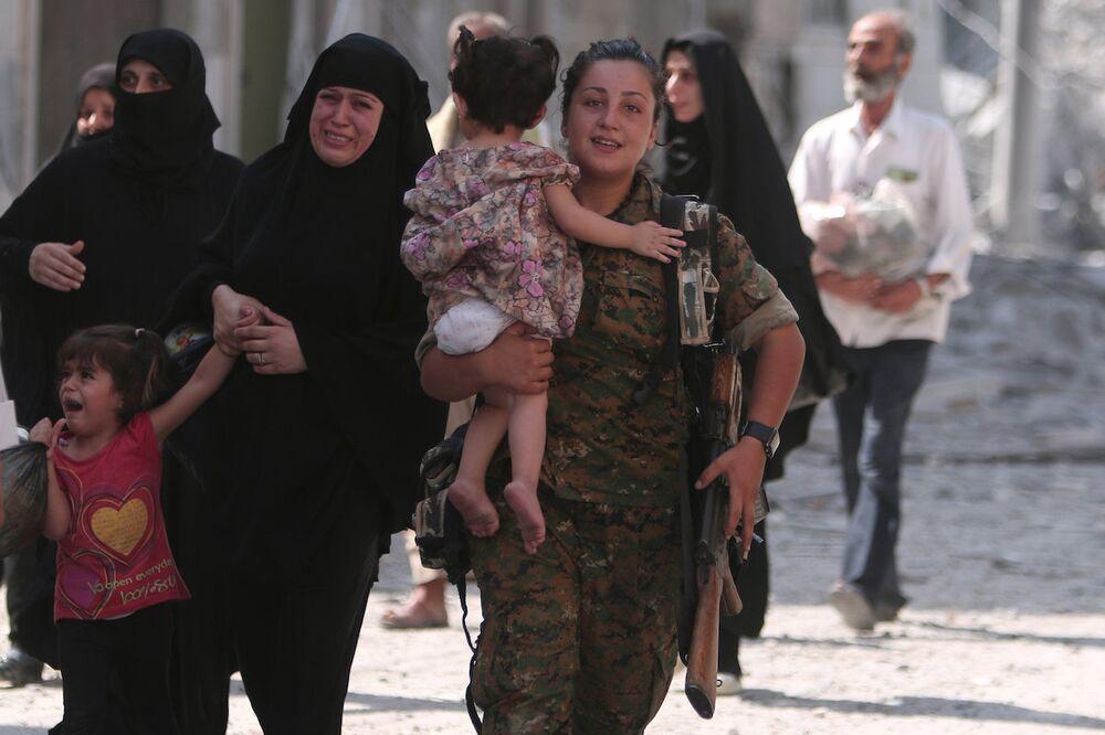Gözü yaşlı Menbiçli kadınlara yardım eden Demokratik Suriye Güçleri askeri.