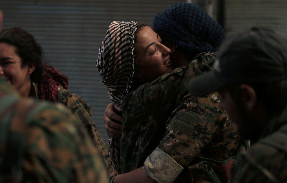 Menbiç'in IŞİD'den kurtarılmasının ardından birbirine sarılan Demokratik Suriye Güçleri kadın askerlari.