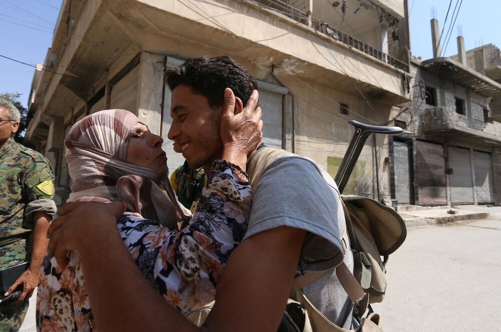 Kente giren Demokratik Suriye Güçleri askerini öpen Menbiçli bir teyze.
