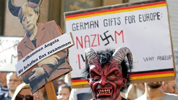 Merkel'i protesto edenler ellerinde 'Almanya'nın Avrupa'ya hediyesi Nazizm ve İslam' ile 'Hoşgeldin Angela, birlikte başarabiliriz' yazılı pankartlar taşıdı. - Sputnik Türkiye