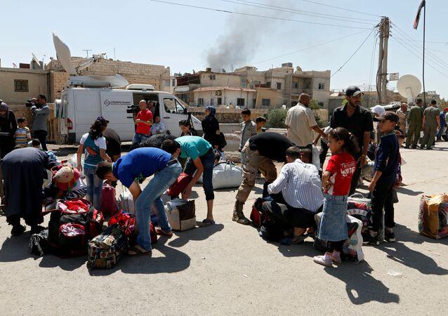 Deraya'da tahliye öncesi otobüs bekleyen siviller