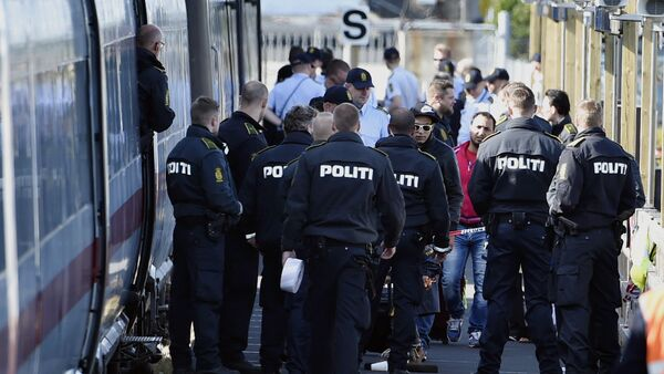 Danish police guards a train with migrants, mainly from Syria and Iraq, at Rodby railway station, southern Denmark - Sputnik Türkiye