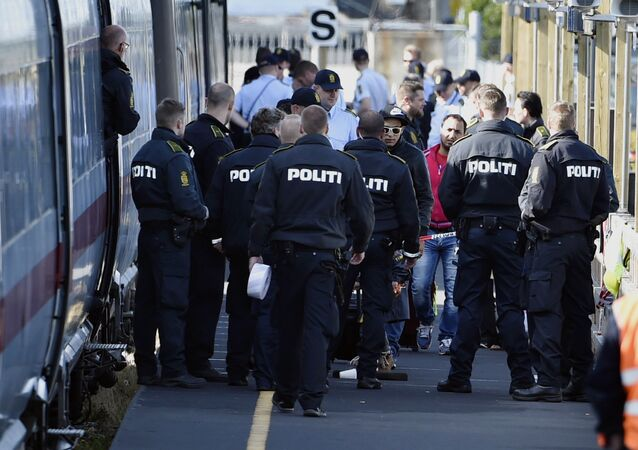Danish police guards a train with migrants, mainly from Syria and Iraq, at Rodby railway station, southern Denmark