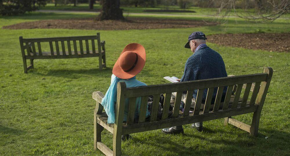Parkta kitap okuyan bir çift. (İngiltere)