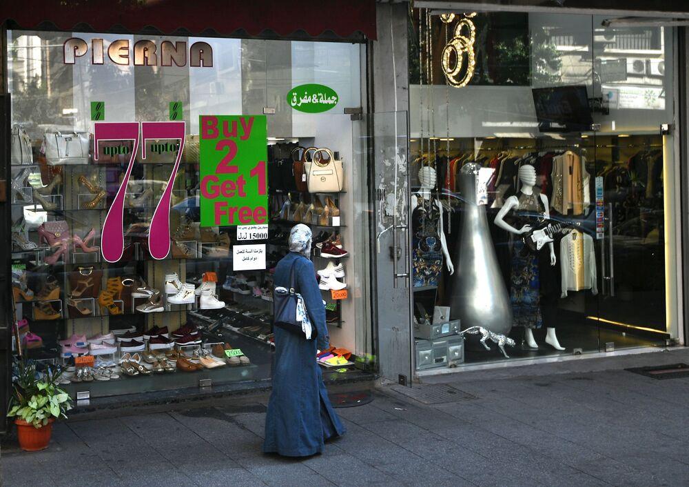 Lübnan'ın Beyrut şehrindeki mağaza vitrinin önündeki kadın.