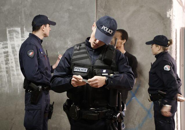 Polis Paris'te bir kişiye kimlik kontrolü yapıyor