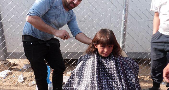 Musul'daki savaştan kaçan çocuklardan biri mülteci kampında saçını kestiriyor.