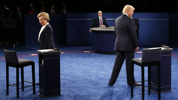 Democratic nominee Hillary Clinton (L) and Republican nominee Donald Trump arrive on stage during the second presidential debate at Washington University in St. Louis, Missouri on October 9, 2016 - Sputnik Türkiye