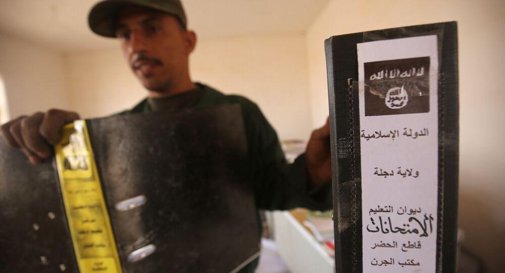 Irak ordusundan bir asker Musul yakınlarında bulunan IŞİD'e ait dokümanı gösteriyor
