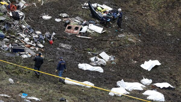 Rescue workers walk next to bodies from the wreckage of a plane that crashed into the Colombian jungle with the Brazilian soccer team Chapecoense onboard near Medellin, Colombia - Sputnik Türkiye