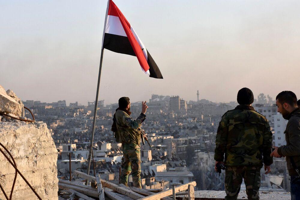 Bir Suriye askeri Halep'te cihatçı gruplardan alınan mahallede zafer pozu veriyor