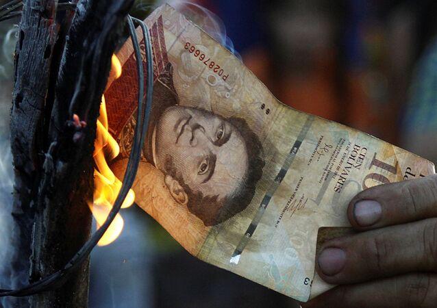 Ekonomik krizi protesto eden bir Venezüellalı eylemci 100 bolivarlık banknotu yakıyor