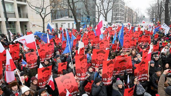 Varşova'daki Anayasa Mahkemesi önündeki eylemciler Anayasa Mahkemesi Başkanı Andrzej Rzeplinski'nin fotoğraflarını taşıyor. - Sputnik Türkiye