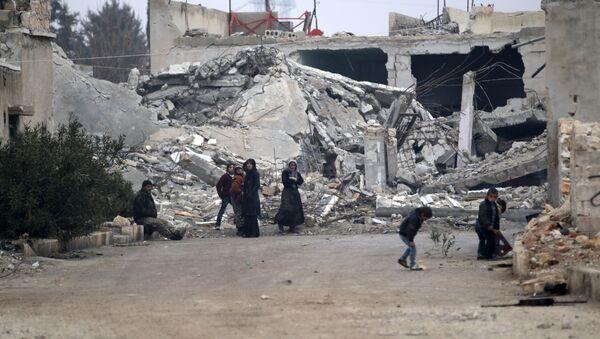 Halep'in kuzetindeki El-Rai'de Suriyeliler bina enkazlarının önünde oturuyor - Sputnik Türkiye