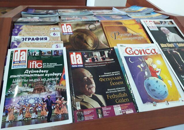 """Rus gazeteci-yazar Glep Prostakov, Kırgızistan'daki Fetüllah Gülen'e ait olduğu iddia edilen Sebat okulunun kütüphanesindeki dergilerin üzerinde Gülen fotoğraflarına dikkat çekerek, """"Bana daha önce okul yönetimi öğrencilerin Gülen'i tanımadıklarını söylemişti"""" dedi."""