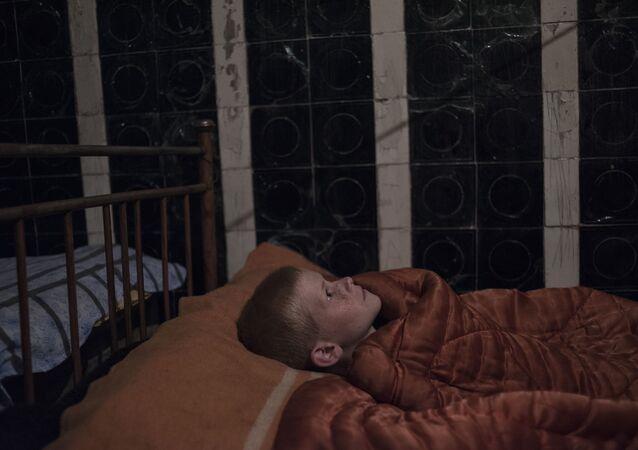 Donbass'ta yıkılan okullardan birinin bodrumuna sığınan bir çocuk.