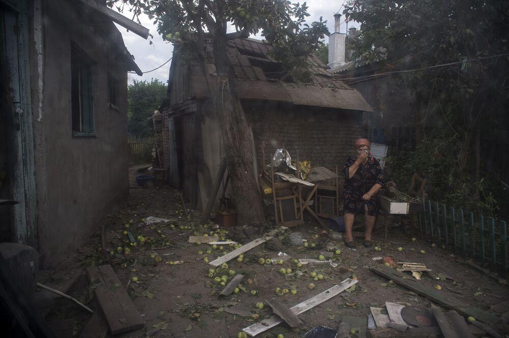 Lugansk sakini, Ukrayna ordusunun topçu saldırısında yıkılan evinin önünde duruyor.
