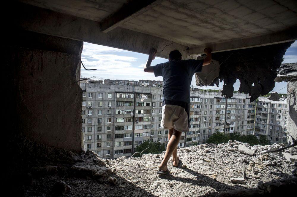 Lugansk'ın Mirniy mahallesine topçu saldırısının ardından bir adam binadaki hasarı inceliyor.